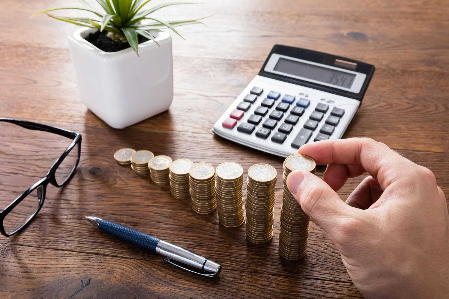 stack of coins being counted with a calculator