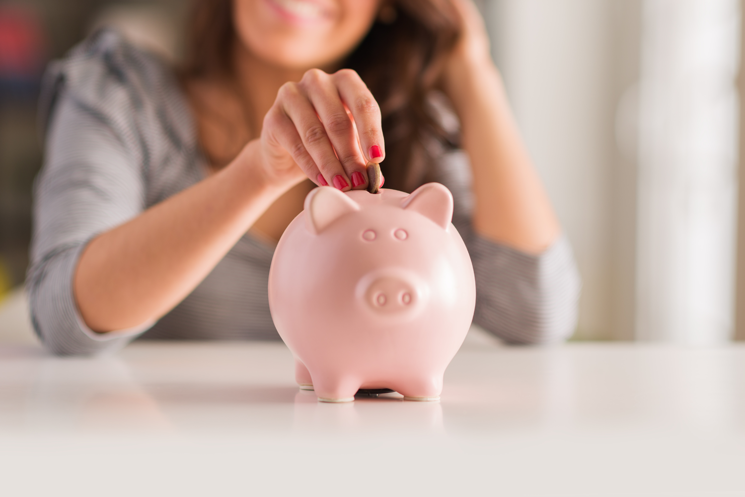 woman saving into a piggy bank